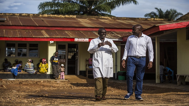 Twp men talking while walking in front of an urgent care center in the Democratic Republic of Congo
