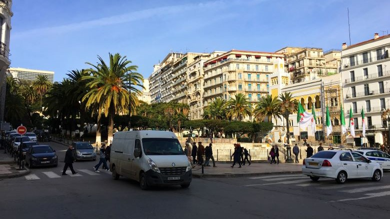 Pedestrians cross the street in a busy traffic intersection in Algeria.