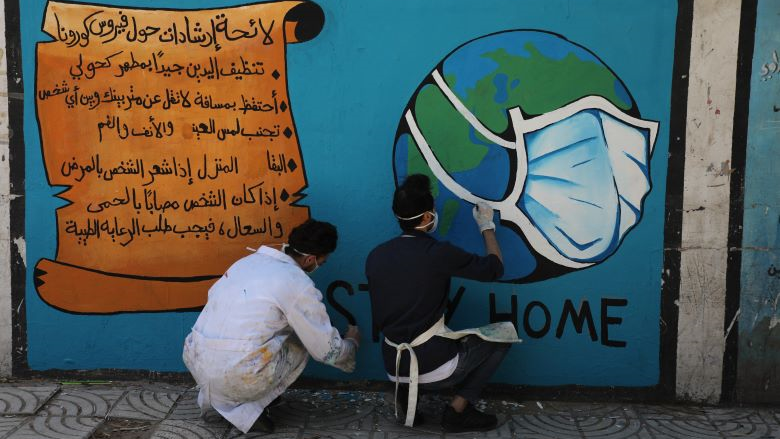 Palestinian artists from Gaza draw a list of instructions to apply in order to stop the spreading of COVID-19 in the Gaza Strip.